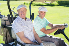 Golfing friends driving in their golf buggy smiling at camera Royalty Free Stock Photography