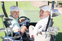 Golfing friends driving in their golf buggy smiling at camera. On a sunny day at the golf course stock image