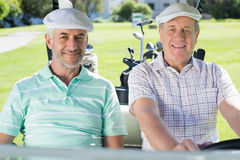 Golfing friends driving in their golf buggy smiling at camera Stock Photos