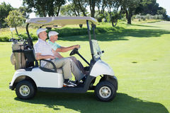 Golfing friends driving in their golf buggy Royalty Free Stock Images