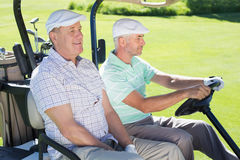 Golfing friends driving in their golf buggy Royalty Free Stock Photo