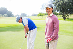 Golfing friends on the putting green Royalty Free Stock Images