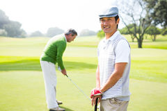Golfing friends on the putting green Royalty Free Stock Image