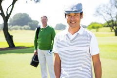 Golfing friends smiling at camera Stock Photography