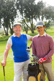 Golfing friends smiling at camera holding clubs. At the golf course stock photos