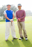 Golfing friends smiling at camera holding clubs Royalty Free Stock Photo