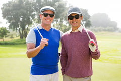 Golfing friends smiling at camera holding clubs Royalty Free Stock Photos