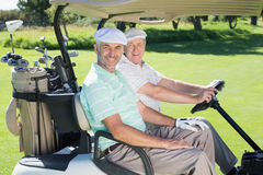 Golfing friends smiling at camera in their golf buggy Stock Images