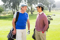 Golfing friends smiling and holding clubs. At golf course stock photo