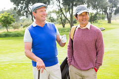 Golfing friends smiling and holding clubs Royalty Free Stock Photography
