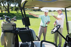 Golfing friends standing beside their buggy looking around Royalty Free Stock Images