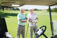 Golfing friends standing beside their buggy looking around Royalty Free Stock Photos