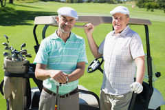 Golfing friends standing beside their buggy smiling at camera Royalty Free Stock Image