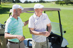 Golfing friends standing beside their buggy smiling Stock Images