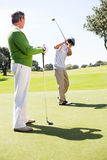 Golfing friends teeing off. At the golf course royalty free stock photography