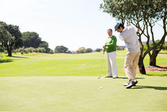 Golfing friends teeing off. At the golf course Royalty Free Stock Images