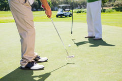 Golfing friends teeing off Royalty Free Stock Images