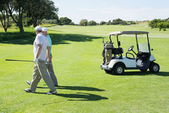 Golfing friends walking beside their buggy Stock Photography