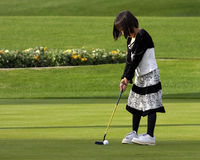 Golfing Girl. A young girl getting ready to putt Stock Image