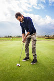 Golfing. A golf player aiming for the hole on the green with a putter Stock Image