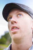 Golfing Handicap. Head Shot Of A Dazed And Confused Golfer Looking Skywards After Being Hit In The Head By A Flying Golf Ball In A Golfing Handicap Concept Stock Photo