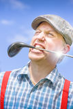 Golfing Mad. Crazy Golfer Man Smiles With Golf Stick In His Mouth While Looking To The Distance After A Tee Off In Playful Sporting Golfing Mad Concept Stock Photography