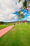 Golfing in Oahu, Hawaii. Golf cart running by the paved road of golf course of Marriott timeshare resort. Oahu, Hawaii royalty free stock photos