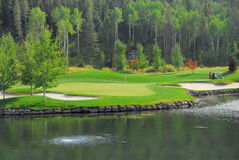 Golfing over the water. Beautiful green golf course with water and sand traps Royalty Free Stock Photography