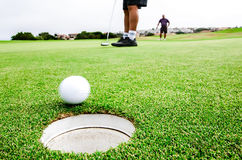 Golfing pairs. The golfers is playing golf mostly in two pairs stock photo