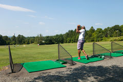 Golfing at the Range. Athletic golfer swinging at the driving range dressed in casual attire Stock Photos