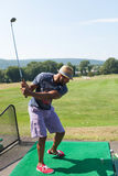 Golfing at the Range. Athletic golfer swinging at the driving range dressed in casual attire Stock Images