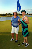 Golfing Senior women. Two senior women playing a round of golf standing on the putting green Stock Images
