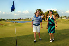 Golfing Senior women. Two senior women playing a round of golf walking off the putting green Stock Image