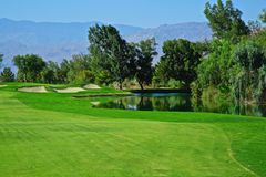 Golfing Shadow ridge golf course Pal Desert California. Beautiful lush green fairway leads to sand traps and hole on the Shadow Ridge Golf Course in Palm Desert stock photos