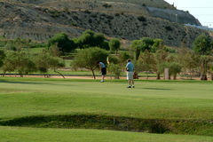 Golfing In Spain. 2 golfers on golf course in Spain Stock Image