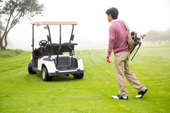 Golfing walking toward the buggy Royalty Free Stock Photo
