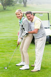 Golfingspaar dat bal zet die samen bij camera glimlacht Stock Foto