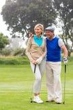 Golfingspaar die op groen zetten lopen Stock Afbeelding