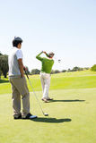 Golfingsvrienden die weg teeing Stock Afbeeldingen