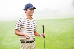 Golfista alegre que sostiene su club y pelota de golf Imagen de archivo libre de regalías