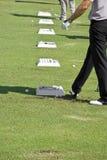 Golfista con la fila de las bolas de la práctica Imagen de archivo libre de regalías