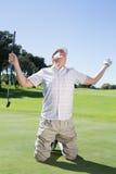 Golfista de arrodillamiento que anima en putting green Fotos de archivo libres de regalías