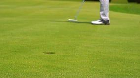 Golfista de la cámara lenta que pone la pelota de golf en el agujero almacen de video
