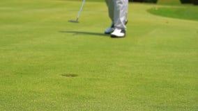 Golfista de la c?mara lenta que pone la pelota de golf en el agujero almacen de video