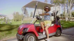 Golfista de la mujer bastante joven en un carro de golf rojo almacen de metraje de vídeo