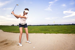 Golfista de la mujer en el desvío de arena que se prepara para golpear la bola. Fotografía de archivo libre de regalías