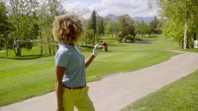 Golfista de la mujer joven con su club sobre su hombro almacen de video