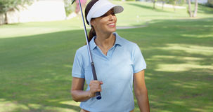 Golfista de la mujer joven que da un paseo a través del curso Imágenes de archivo libres de regalías