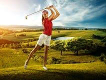 Golfista de la mujer que golpea la bola en el paisaje del fondo hermoso Foto de archivo