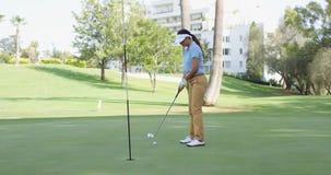 Golfista de la mujer que se alinea para un putt Imagen de archivo libre de regalías